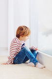Handsome young boy sitting on carpet near the window at rainy day stock images
