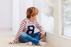 Handsome young boy sitting on carpet near the window at rainy day royalty free stock image