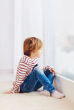 Handsome young boy sitting on carpet near the window at rainy day royalty free stock photography