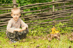 Handsome young boy squatting alongside a fire Royalty Free Stock Photography