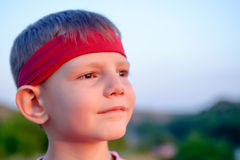 Handsome young boy staring into the distance. Close up of the face of a handsome young boy wearing  red headband staring distance setting sun dreamy expression Royalty Free Stock Image