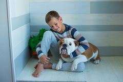 Handsome Young Boy wearing cozy pajamas Playing with His english funny bull Dog and enjoy life time weekend hanging each other