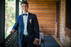 Handsome young bridegroom standing by window Stock Images