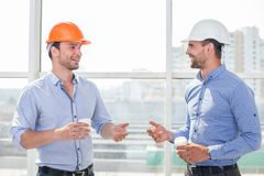 Handsome young builders are relaxing after work. Cheerful architect and foreman are drinking coffee. They are talking about new project with inspirations and royalty free stock image