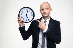 Handsome young business man in black suit pointing on clock Stock Image