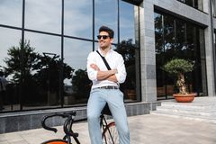 Handsome young business man dressed white shirt. Outdoors, sitting on a bicycle stock photo