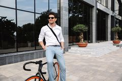 Handsome young business man dressed white shirt. Outdoors, sitting on a bicycle stock photography
