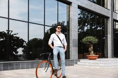 Handsome young business man dressed white shirt. Outdoors, sitting on a bicycle stock photos