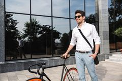Handsome young business man dressed white shirt. Walking outdoors with bicycle royalty free stock images