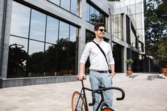 Handsome young business man dressed white shirt. Walking outdoors with bicycle royalty free stock photography
