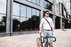 Handsome young business man dressed white shirt. Walking outdoors with bicycle stock image