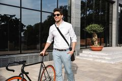 Handsome young business man dressed white shirt. Walking outdoors with bicycle royalty free stock image
