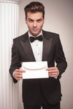 Handsome young business man giving you a white envelope. Royalty Free Stock Images