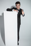 Handsome young business man leaning on a white board Stock Images