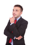 Handsome young business man looking up. While holding his hand to his chin thinking Stock Photography