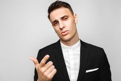 Handsome young business man, male, in a classic black suit, points the finger at the camera, against a gray background. royalty free stock photo