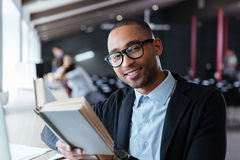 Handsome young business man reading a book at his desk Stock Image