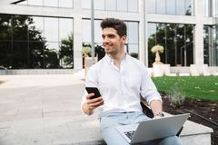 Handsome young business man sitting outdoors using laptop computer and mobile phone stock photo