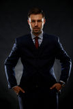 Handsome young business man standing on black Royalty Free Stock Photography