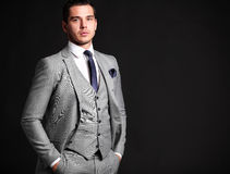 Handsome young business man standing on black. Background Stock Photo