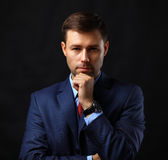 Handsome young business man standing on black Stock Photo