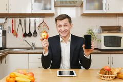 Handsome caucasian young man, sitting at table. Healthy lifestyle. Cooking at home. Prepare food. stock image