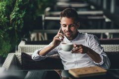 Handsome young business man, talking on the phone and smiling while a enjoying the cup of coffee in cafe.  royalty free stock photography