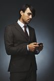 Handsome young business man texting on his phone. Male executive reading test message on his mobile phone. Male model in business suit holding cell phone on Stock Images