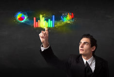Handsome young business man touching colorful modern graph syste Royalty Free Stock Photo