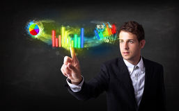 Handsome young business man touching colorful modern graph syste Stock Photo
