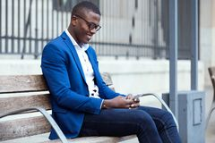 Handsome young business man using his mobile phone in the street Royalty Free Stock Images