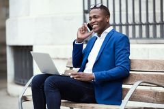 Handsome young business man using his mobile phone while using laptop in the street. Stock Photography