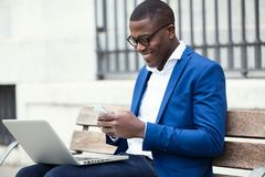 Handsome young business man using his mobile phone while using laptop in the street. Stock Photos