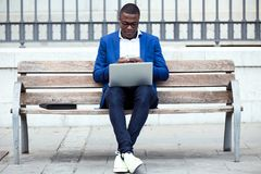 Handsome young business man using his mobile phone while using laptop in the street. Royalty Free Stock Photography