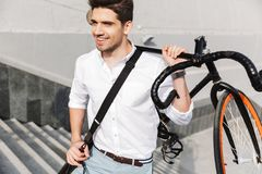 Handsome young business man walking outdoors with bicycle. Image of a handsome young business man walking outdoors with bicycle stock photo