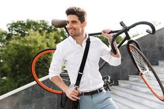 Handsome young business man walking outdoors with bicycle. Image of a handsome young business man walking outdoors with bicycle royalty free stock photography
