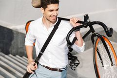 Handsome young business man walking outdoors with bicycle. Image of a handsome young business men walking outdoors with bicycle stock images