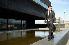 Handsome young business man walking in the street Stock Image