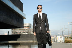 Handsome young business man walking in the street Stock Photo
