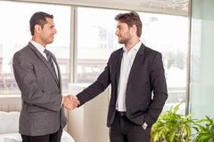 Handsome young business partners build a consensus. Attractive businessmen are shaking hands. They are looking at each other and smiling. They are standing in Royalty Free Stock Photography