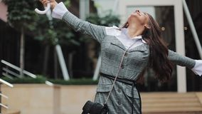 Handsome young business woman looking up the sky and raising hand for checking if the rain stop. She smiling and close stock video footage