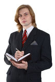Handsome young businessman. With long hair writing in notebook or diary Stock Photos