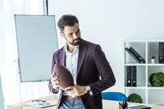 handsome young businessman with american football ball