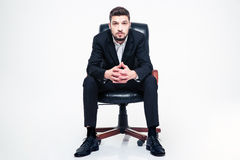 Handsome young businessman with beard sitting in black office chair Stock Images