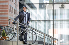 Handsome young businessman carrying bicycle down steps Royalty Free Stock Photos