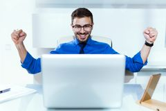 Handsome young businessman celebrating a victory while working with laptop in the office. Stock Photography