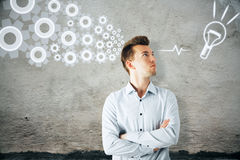 Innovation concept. Handsome young businessman on concrete wall background with drawn cogwheels and lamp. Innovation concept Royalty Free Stock Photography