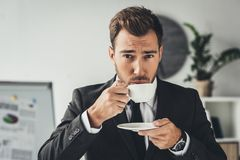 Handsome young businessman drinking coffee. At office Stock Images