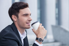 Handsome young businessman is enjoying hot drink Stock Image