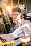 Handsome young businessman in eyeglasses holding newspaper and looking away. In bus royalty free stock images